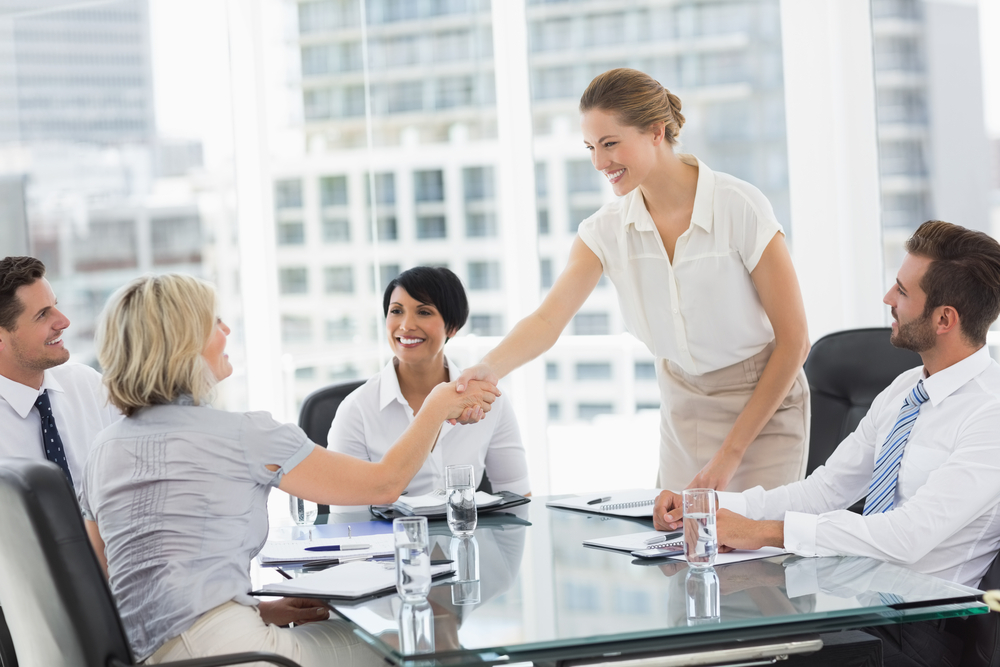 Side view of executives shaking hands during a business meeting in the office